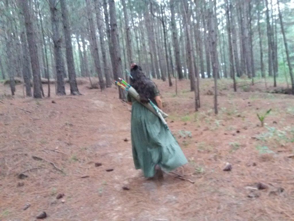 Ninfa do amor caminhando na floresta com arco e flecha para praticar arquearia meditativa