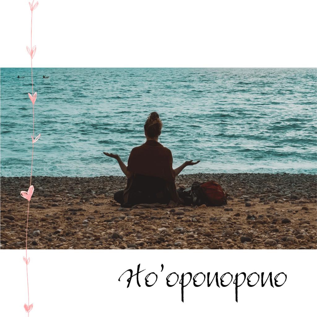 uma mulher sentada na areia da praia, virada de frente para om mar com as palmas da mão para cima como em agardecimento
