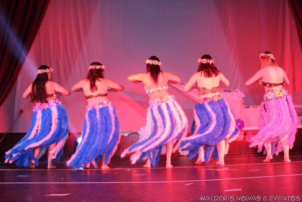 no palco, cinco bailarinas viradas de costas vestidas de Havaianas.