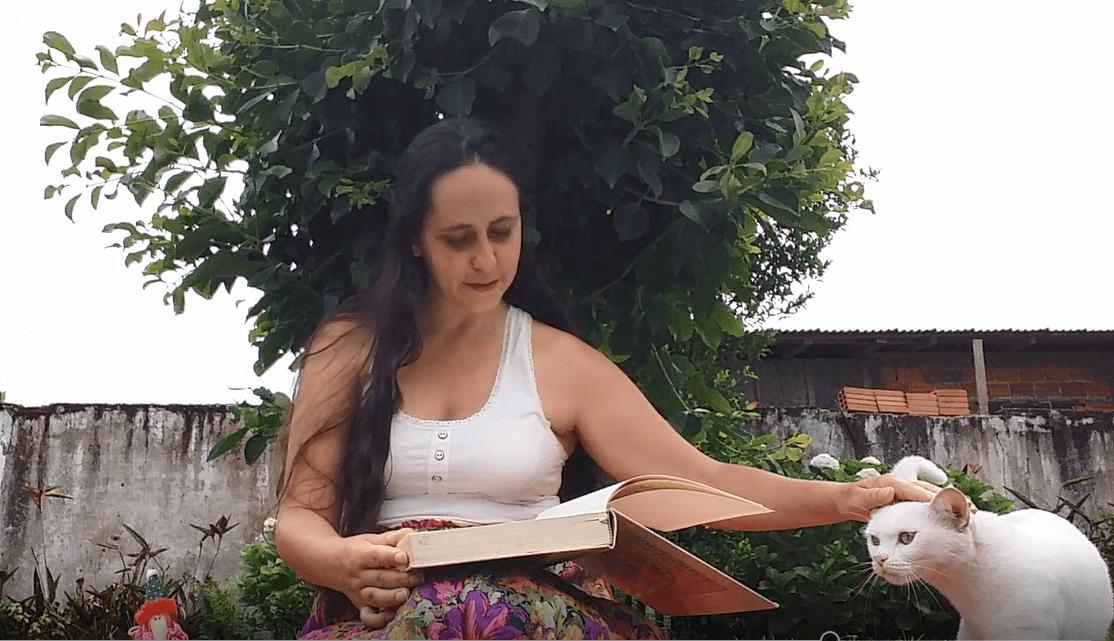 terapeuta Scharlene lendo um livro e acariciando um gato branco.