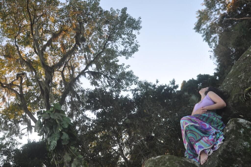 Scharlene Amarante deitada numa pedra olhando para o céu